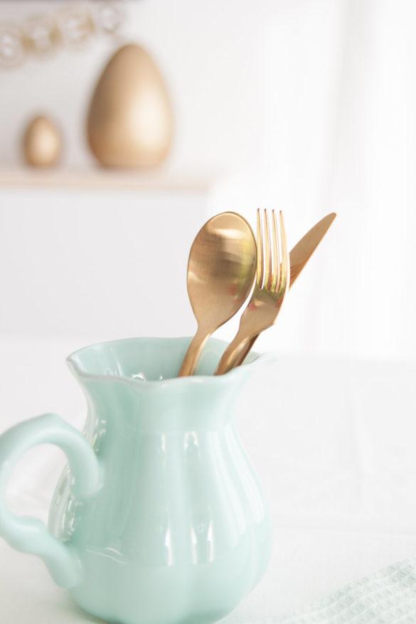 Goldenes Besteck im mintfarbenem Krug