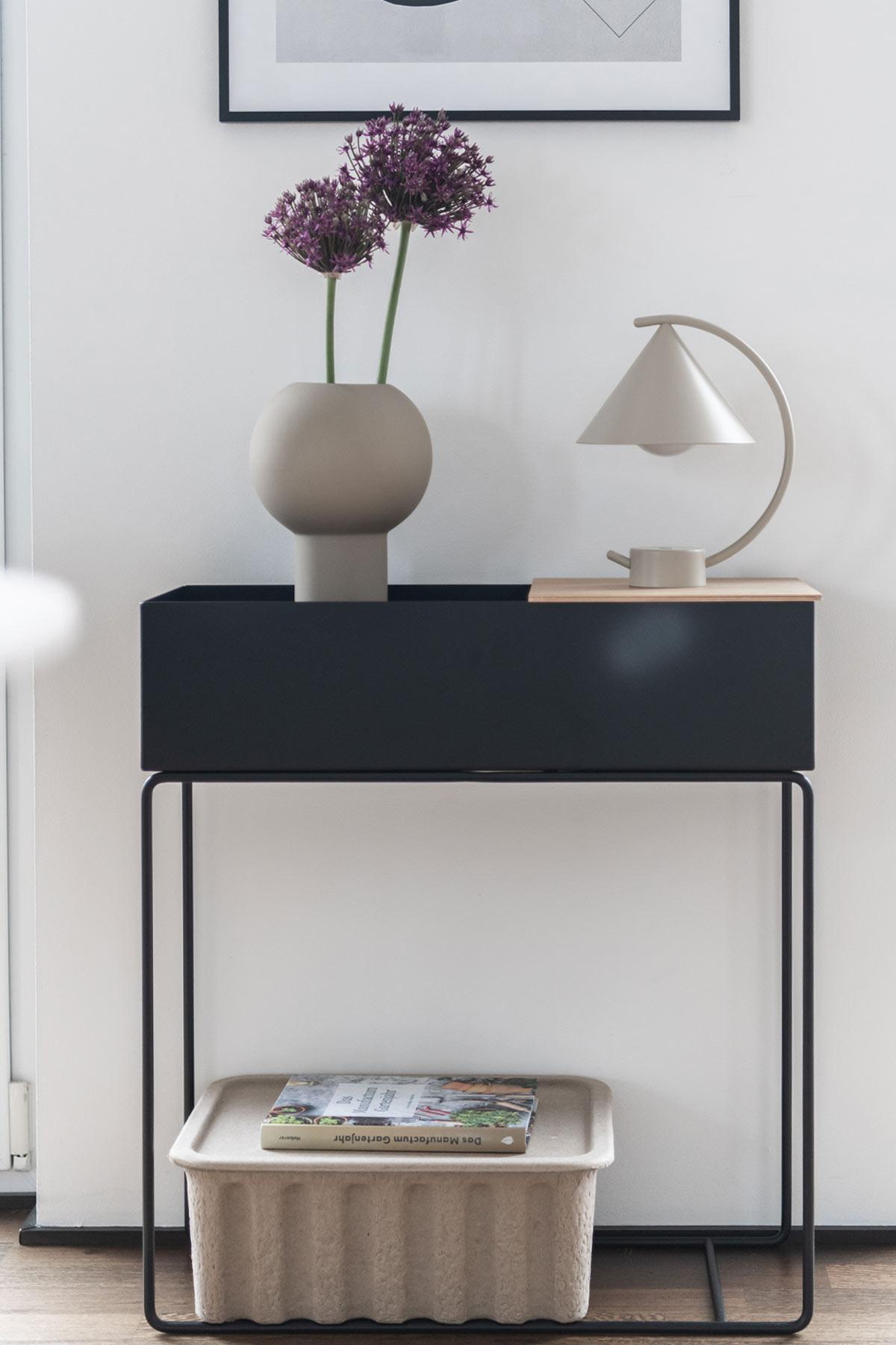 schwarze Plantbox mit Vase und Leuchte